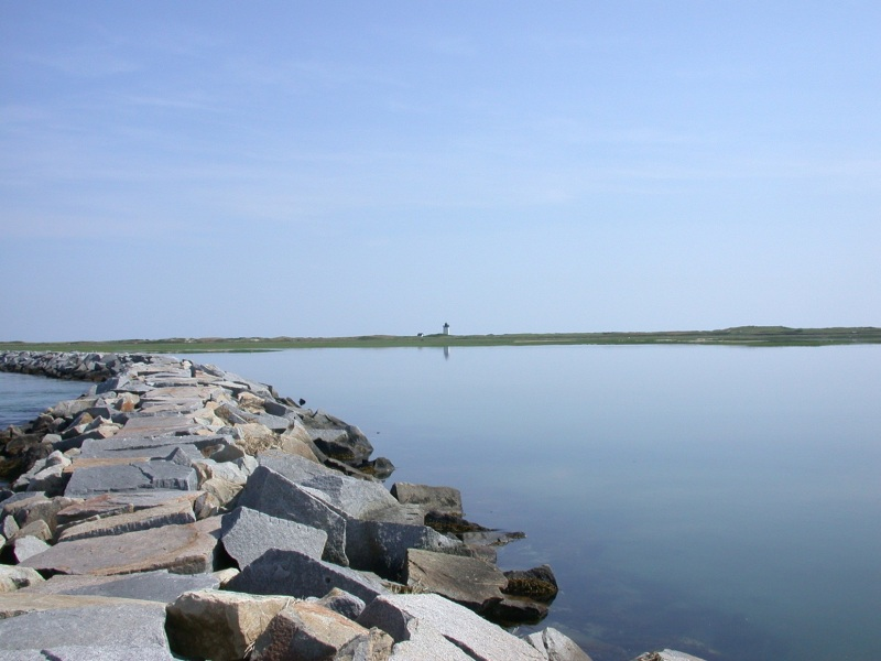 Breakwater in Provincetown, Cape Cod with a lighthouse in the background.